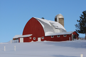 Red barn with tin roof,silo,attached sheds on snow covered hill.